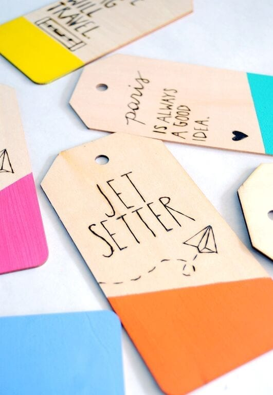 Wooden luggage tags with phrases etched into them and a brightly painted bottom by Best Friends For Frosting